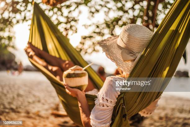 woman with coconut drink relaxing in hammock at the beach. - coconut water stock pictures, royalty-free photos & images