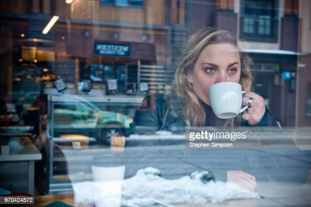 woman with coffee cup in window of cafe - small town america stock pictures, royalty-free photos & images
