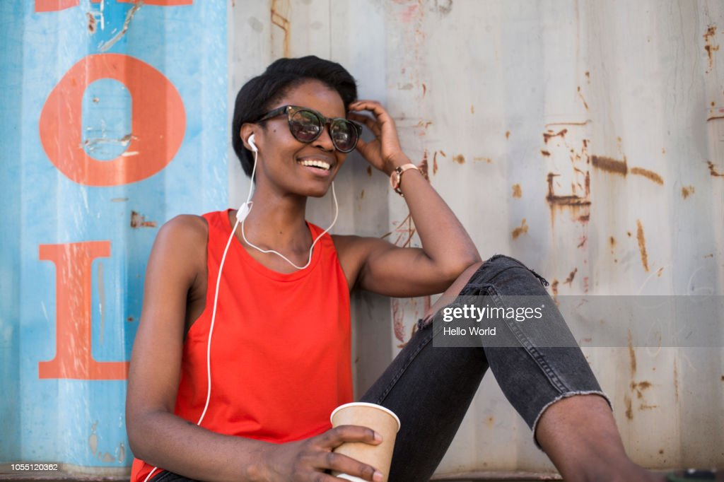 Woman with coffee cup listening to headphones : Stock Photo