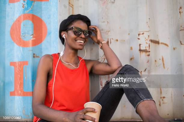 Woman with coffee cup listening to headphones