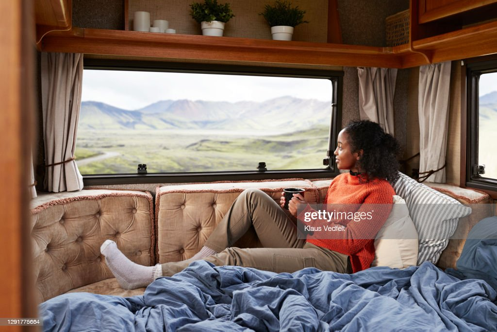 Woman with coffee cup on bed in camper van : Stock Photo
