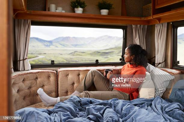 woman with coffee cup on bed in camper van - camper trailer stock pictures, royalty-free photos & images