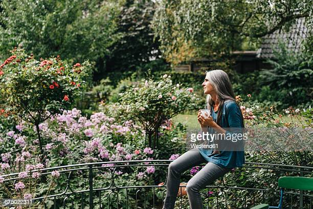 Woman with coffee mug sitting on railing of balcony looking at distance