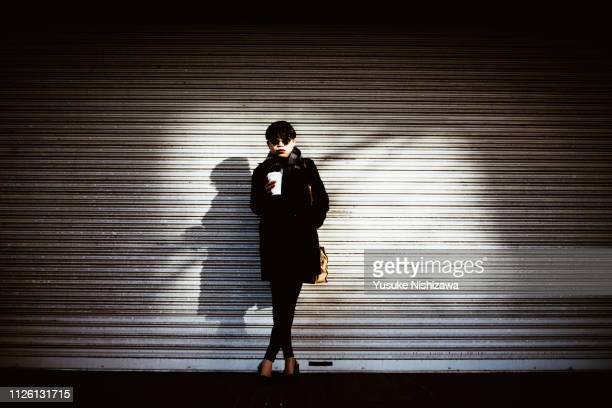 a woman with coffee - yusuke nishizawa stock-fotos und bilder