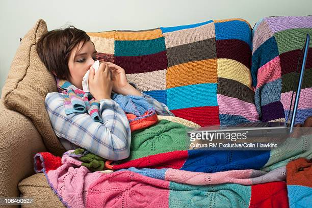 Woman with cold on computer at home
