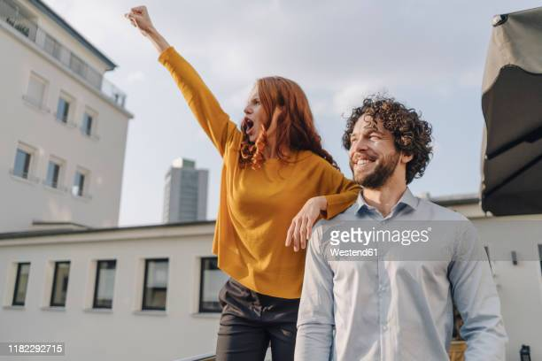 woman with colleague on roof terrace clenching fist - selbstvertrauen stock-fotos und bilder