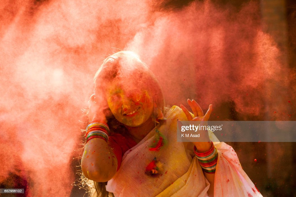 UNIVERCITY, DHAKA, BANGLADESH - : A woman with color powder attend celebrate the Holi Festival or Festival of Colors after smearing each other with colored powder in Dhaka, Bangladesh. Holi festival is celebrated on the full moon day in the month of Phalguna and marks the start of the spring season.