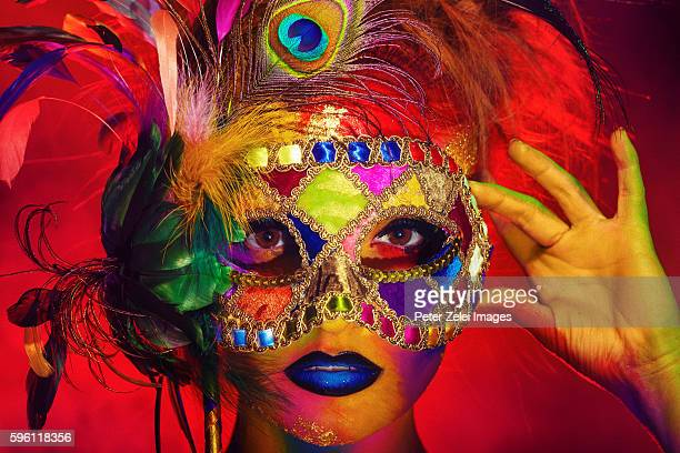 woman with colorful body painting holding a venetian mask decorated with peacock feathers