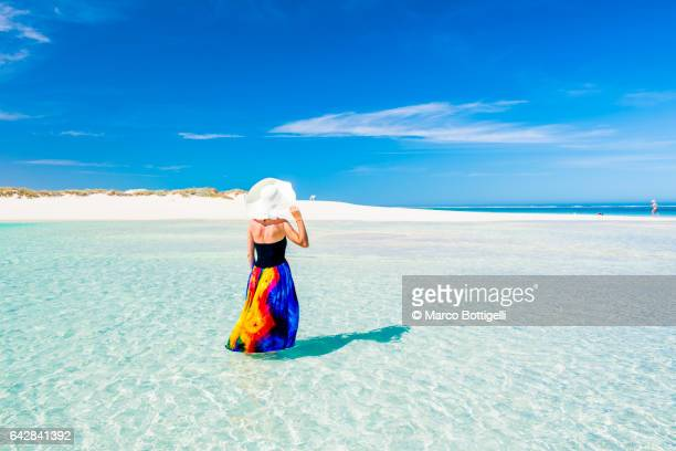 Woman with colorful dress standing on the turquoise water. Western Australia.