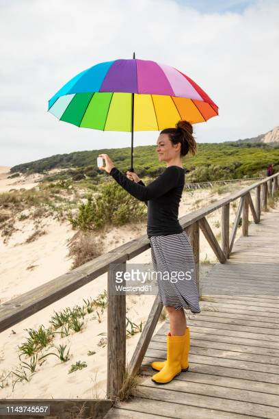 woman with colorful umbrella standing on the beach, taking a selfie - free up skirt pics stock photos and pictures