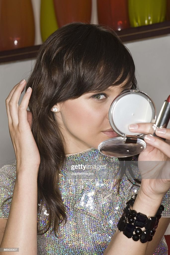 Woman with compact mirror : Stock Photo
