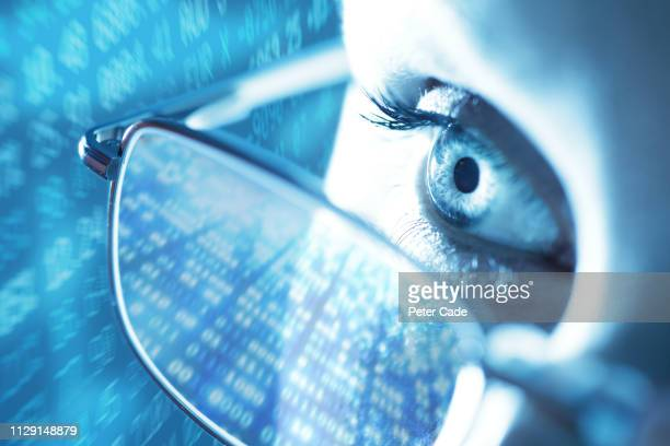 woman with computer screen reflecting in glasses - computer equipment stock pictures, royalty-free photos & images