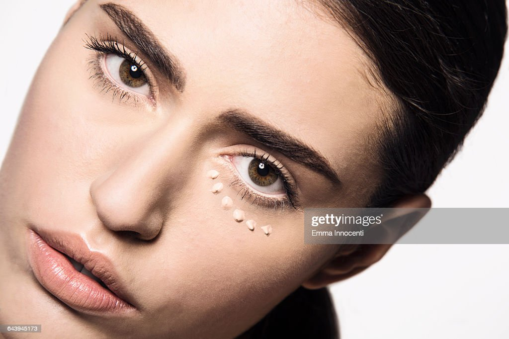 woman with concealer dots under eye : Stock Photo