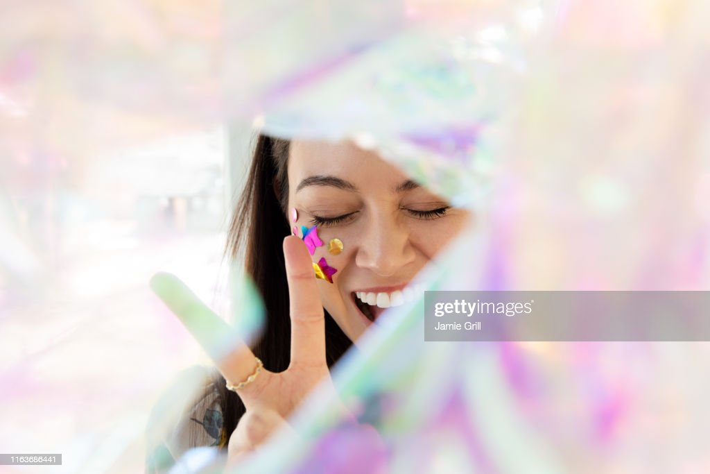 Woman with confetti on cheek making peace gesture : Stock Photo