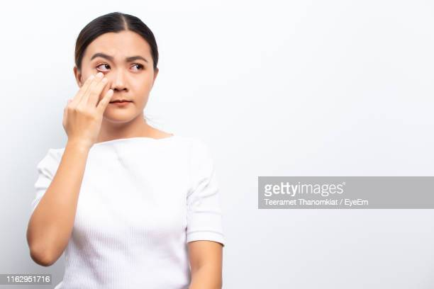 woman with conjunctivitis standing against white background - conjunctivitis stock pictures, royalty-free photos & images