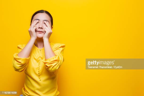 woman with conjunctivitis standing against yellow background - conjuntivite imagens e fotografias de stock