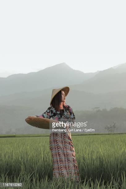 woman with container standing on land against clear sky - java indonesia fotografías e imágenes de stock