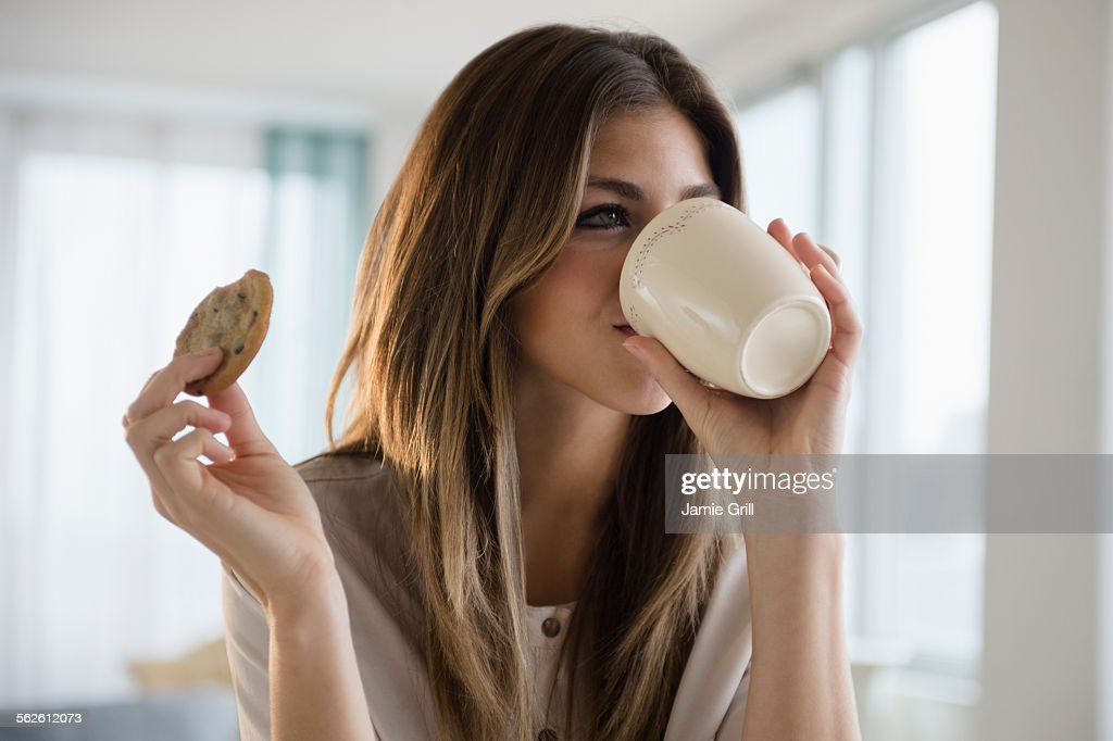 Woman with cookie and coffee : ストックフォト
