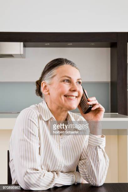 woman with cordless phone at breakfast table - 50 59 years stock pictures, royalty-free photos & images