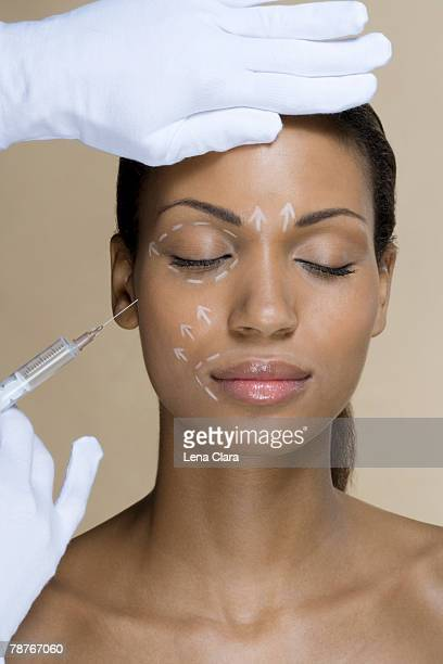 a woman with cosmetic surgery pen marks on her face - beige glove stock photos and pictures
