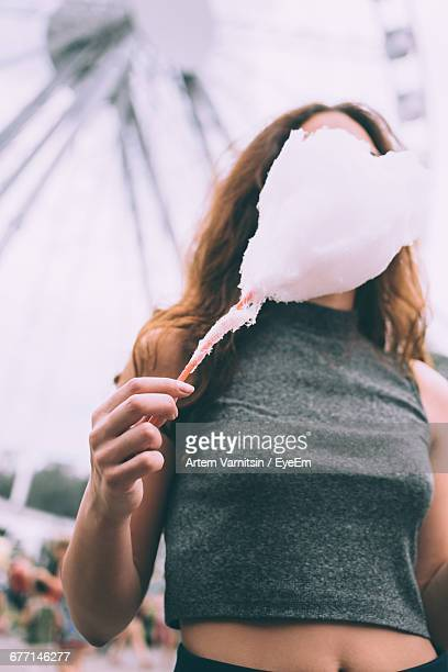 woman with cotton candy against ferris wheel at amusement park - crop top stock pictures, royalty-free photos & images