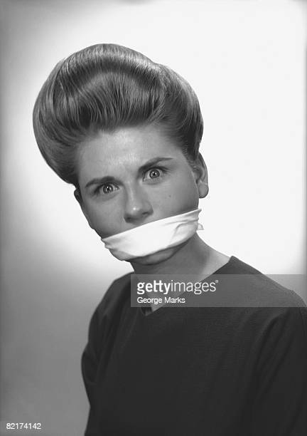 woman with covered mouth in studio, (b&w), portrait - gagged woman stock pictures, royalty-free photos & images