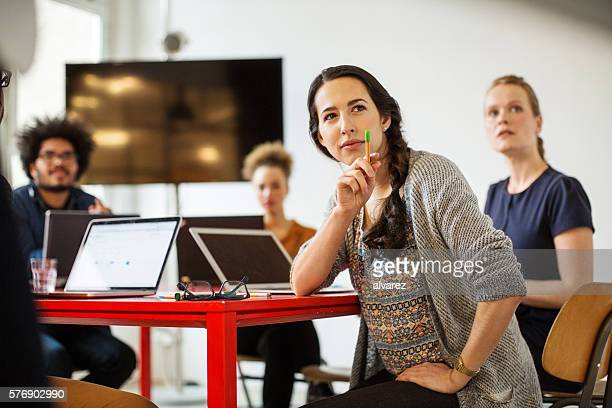 woman with coworkers in conference room - vortrag stock-fotos und bilder