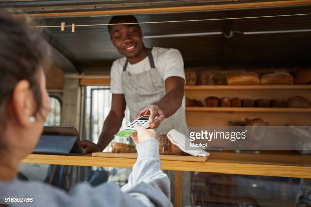 woman with credit card paying salesman at food truck - spending money stock pictures, royalty-free photos & images