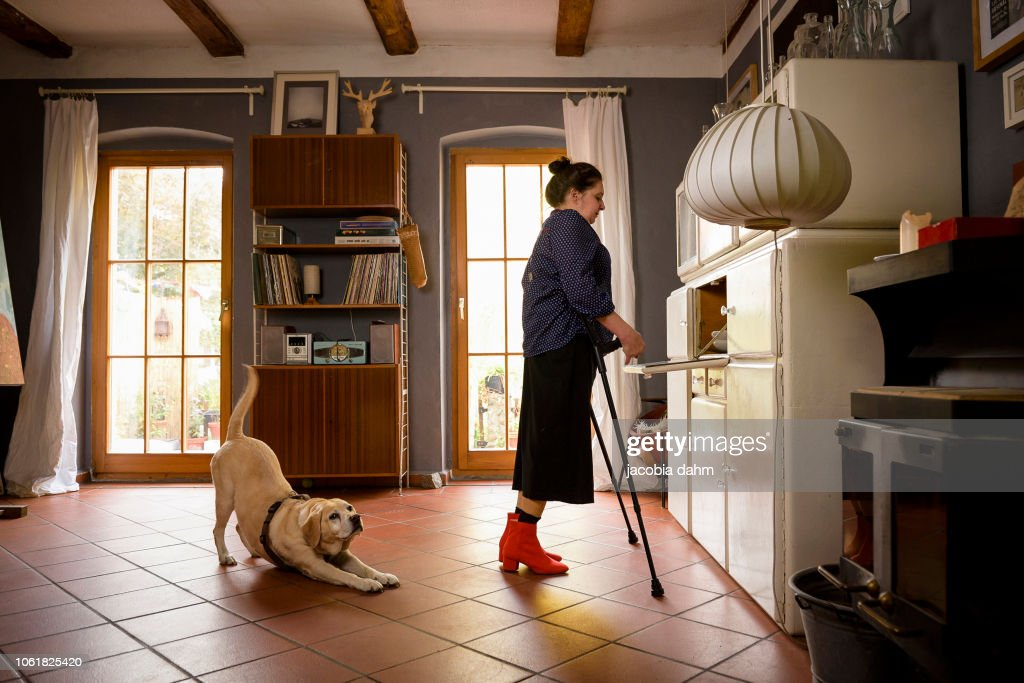 Woman with crutches, with her dog : Stock-Foto