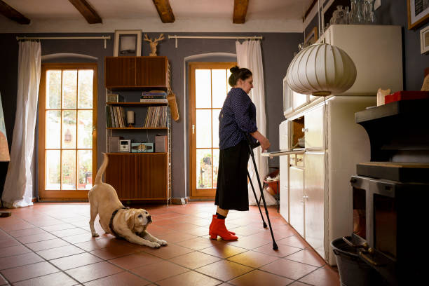 Woman with crutches, with her dog