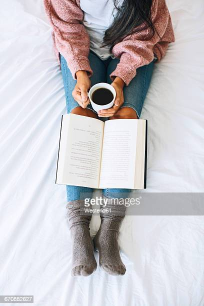 woman with cup of coffee and book relaxing on bed, partial view - indulgenza foto e immagini stock
