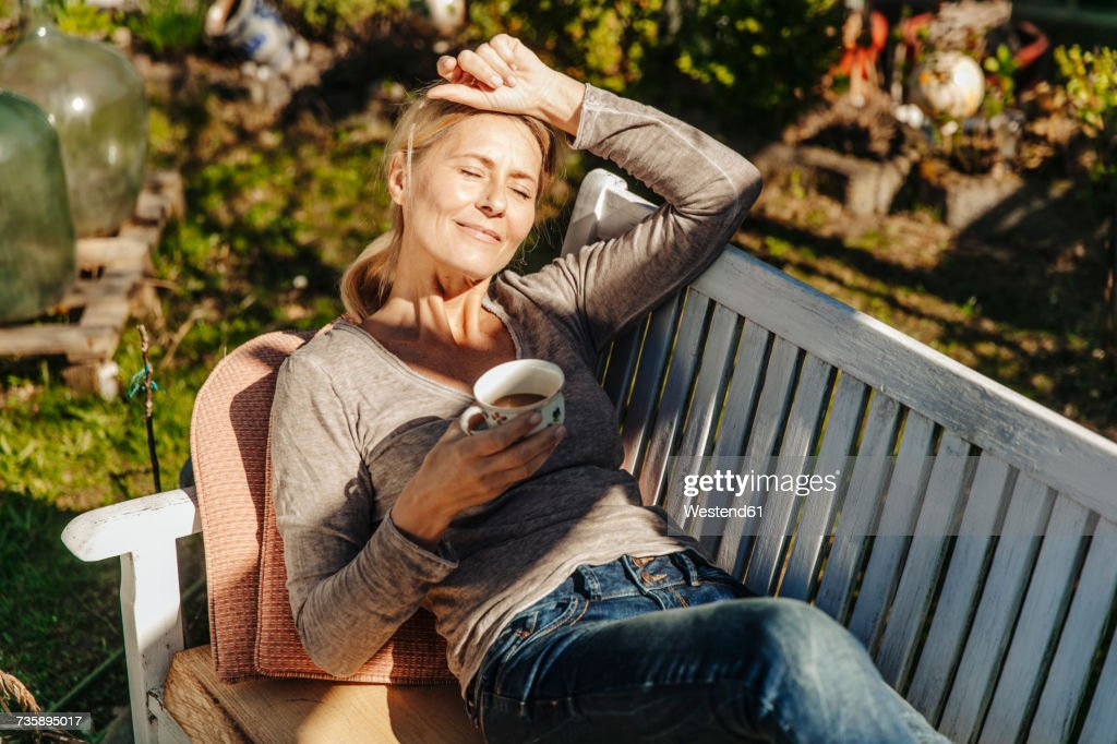 Woman with cup of coffee relaxing on garden bench : Stockfoto