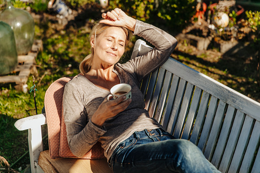 Woman with cup of coffee relaxing on garden bench - gettyimageskorea