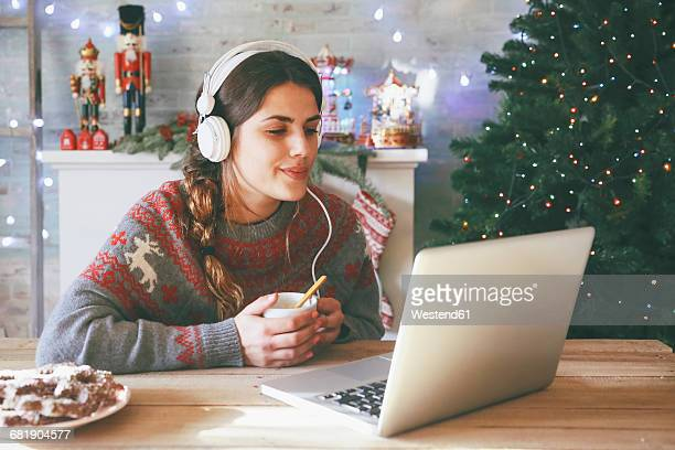 woman with cup of coffee using laptop and headphones at christmas time - christmas music stock pictures, royalty-free photos & images