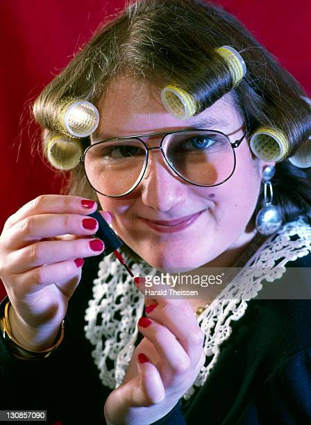 woman with curlers and thick spectacles nail varnish polish grinning - very ugly women stock photos and pictures