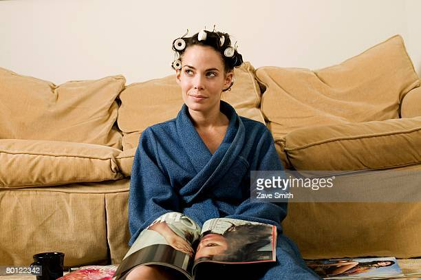 Woman with curlers in hair reading magazine