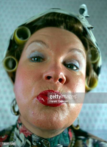 woman with curlers making a grimace - very ugly women stock photos and pictures