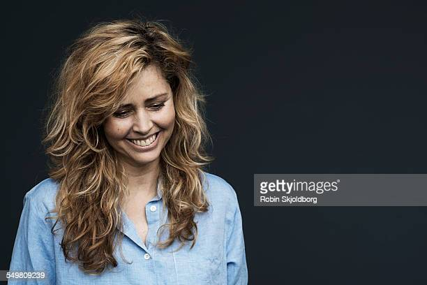 woman with curly hair and blue shirt looking down - robin skjoldborg stock pictures, royalty-free photos & images