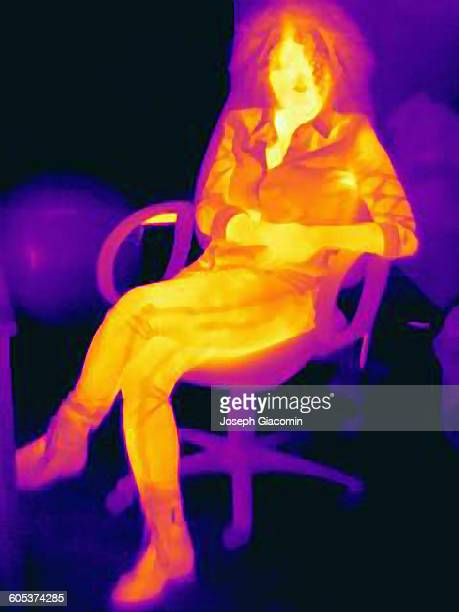 Woman with curly hair on chair, thermal image