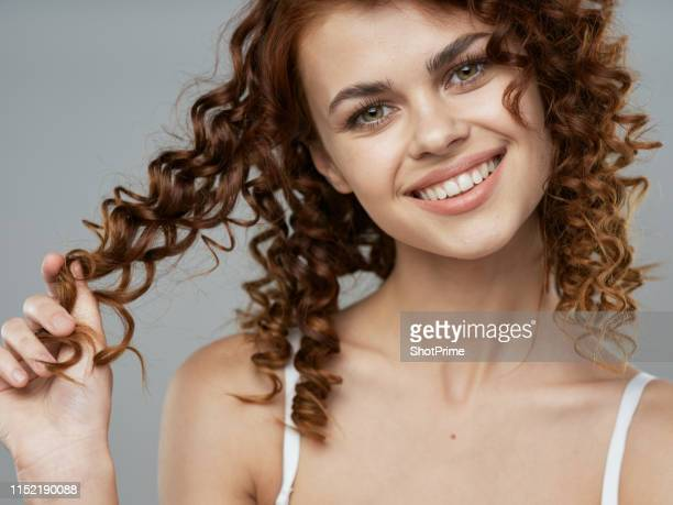 woman with curly hair smiles beautifully and looks into the camera - thick black woman stock photos and pictures