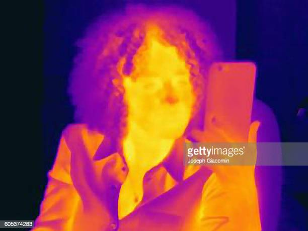 Woman with curly hair using smartphone, thermal image