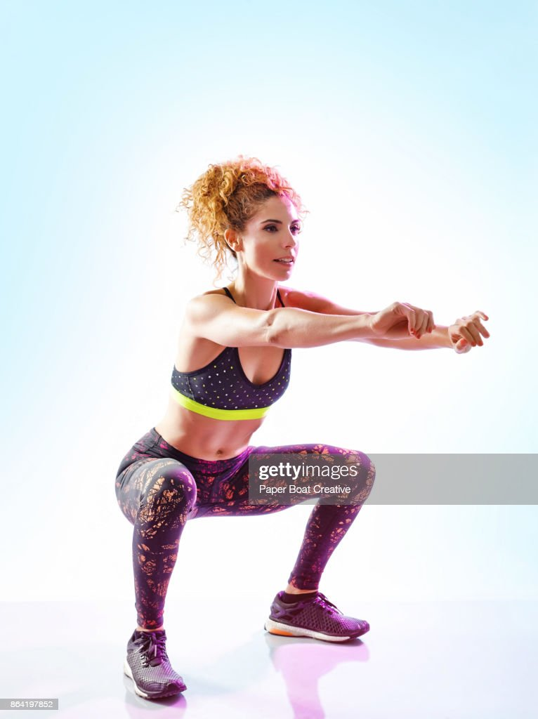 Woman with curly red hair smiling while doing air lunge : ストックフォト