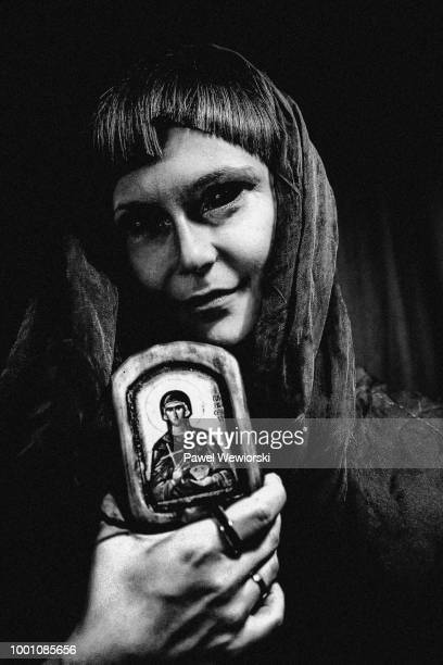 woman with dark eyes holding picture with virgin mary - mary moody fotografías e imágenes de stock