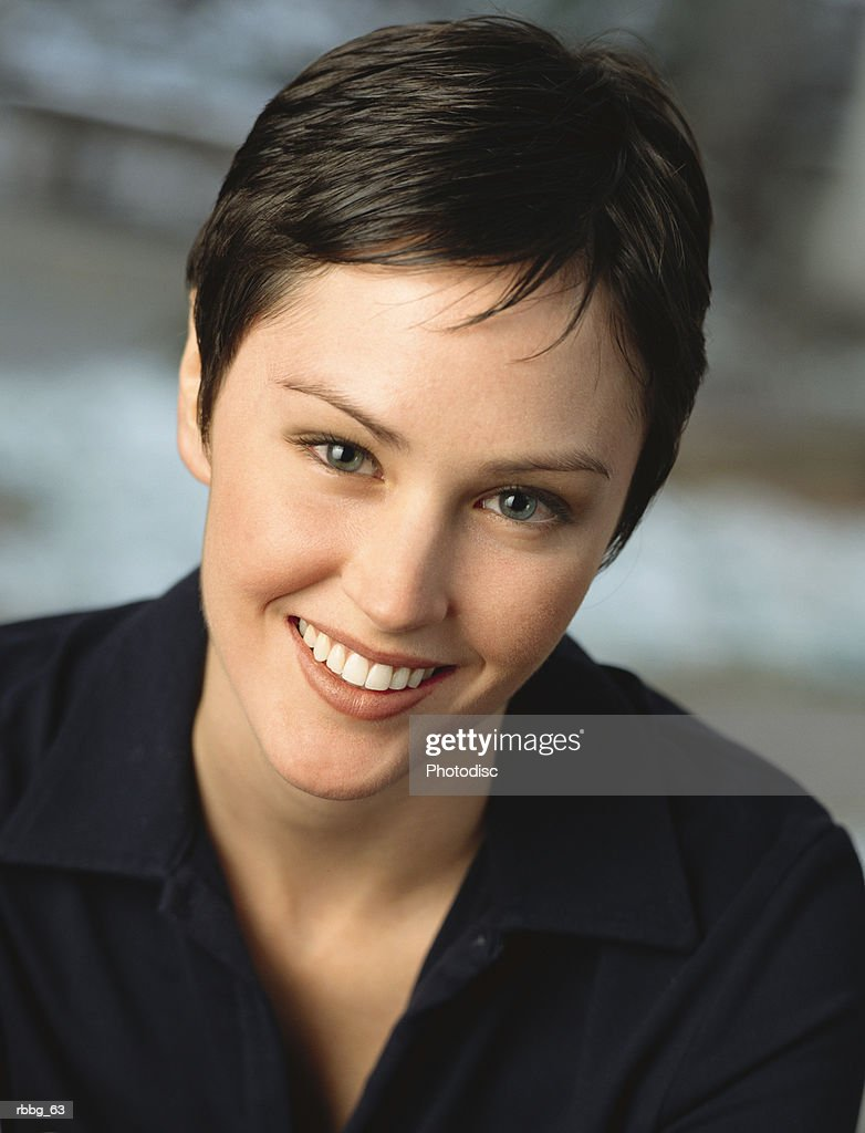woman with dark short hair smiling at the audience with blurred background : Stockfoto