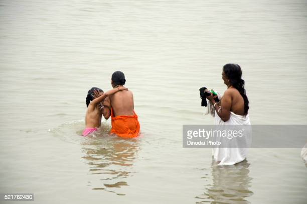 Woman with daughter bathing in Hooghly river, Kolkata, West Bengal, India, Asia