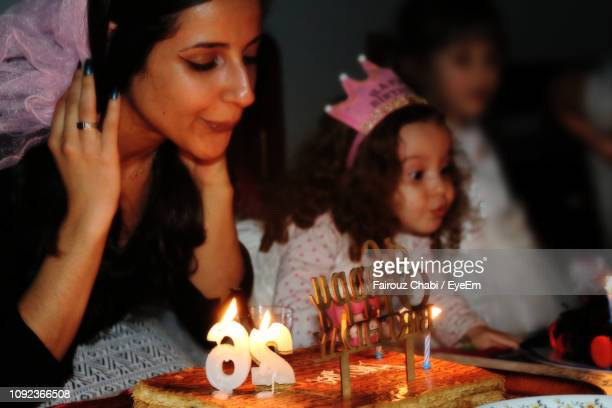 woman with daughter blowing candles in darkroom - daughters of darkness stock pictures, royalty-free photos & images
