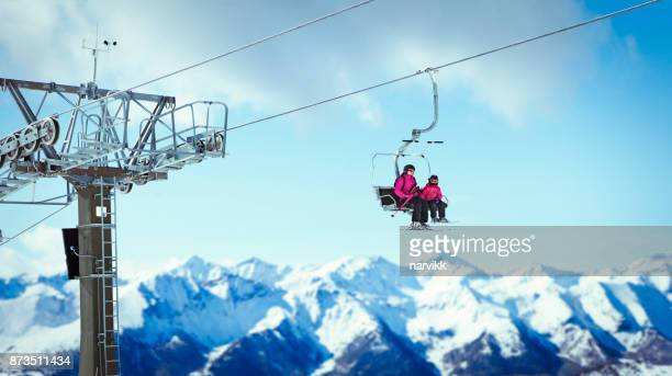 woman with daughter going on the ski lift - ski lift stock pictures, royalty-free photos & images
