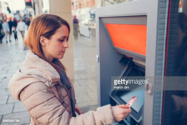 Woman with debit card at the ATM