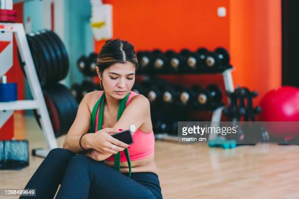 woman with diabetes checking blood sugar levels after sports training - glycemia stock pictures, royalty-free photos & images