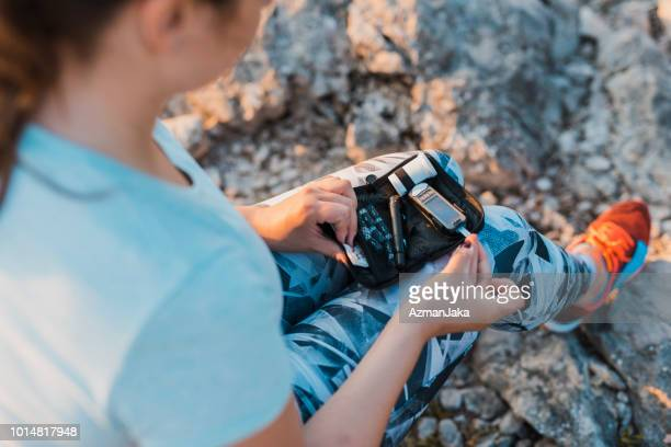 woman with diabetes checking her blood glucose using her glucose meter - checking sports stock pictures, royalty-free photos & images